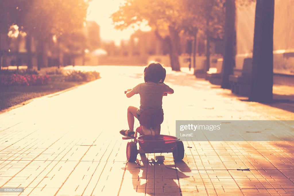 Little girl(2-3) on tricycle in park