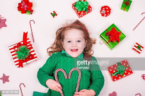 Little girl opening Christmas presents : Stock Photo