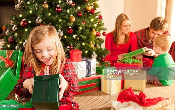 Little girl opening gift on Christmas morning, family in background