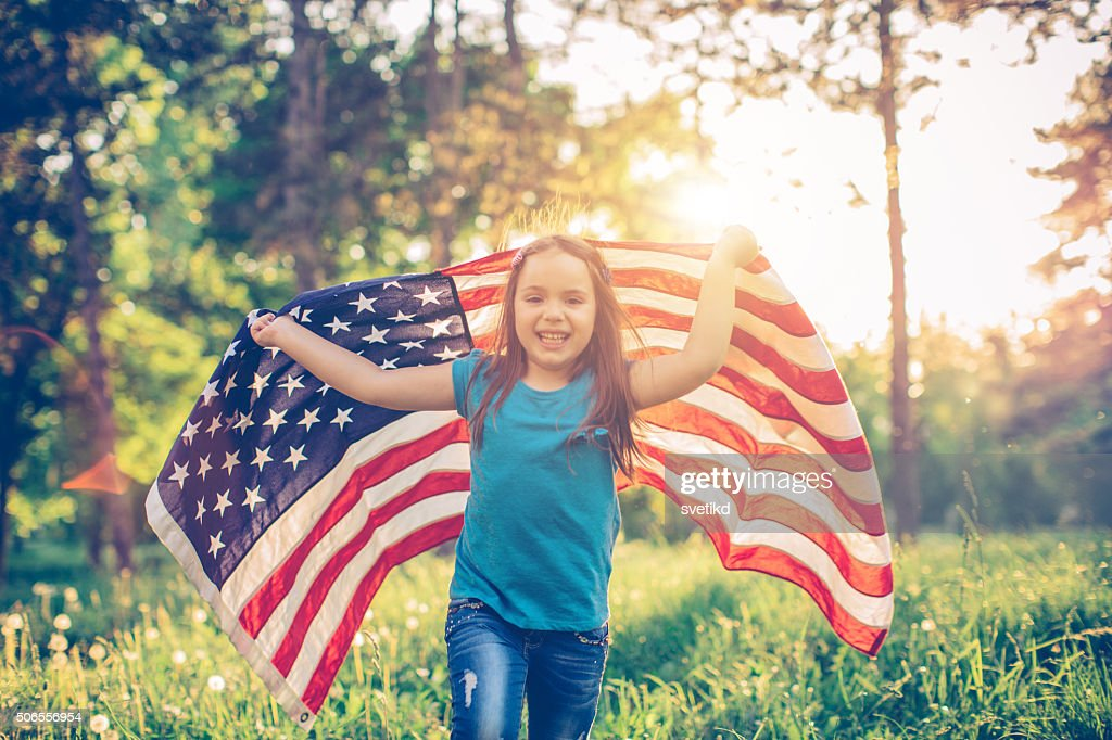 Little girl outdoors in a meadow on july 4th : Stock Photo