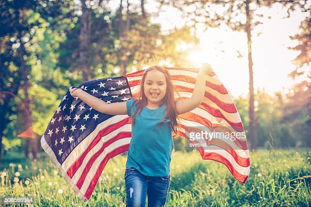 Little girl outdoors in a meadow on july 4th