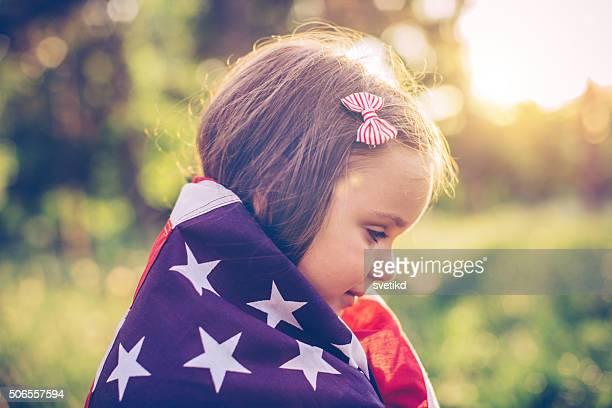 Kleines Mädchen im Freien in einer Wiese am 4. Juli