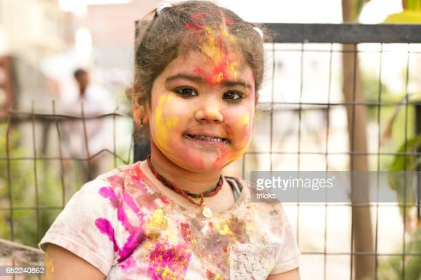 Little girl painted her face with multi colors