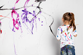 Little girl painting a white wall with colorful paint. Messy fun. Child's creativity development.