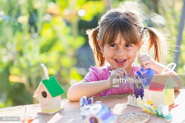 Little girl painting bird house