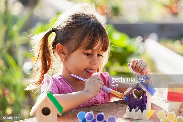 Little girl painting bird house