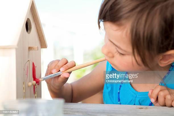 Little girl painting birdhouse