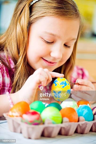 Kleines Mädchen malen Ostereier.