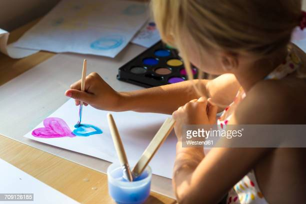 Little girl painting hearts with watercolours
