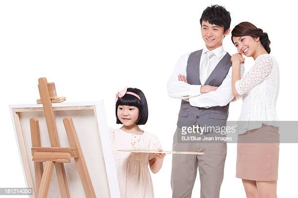 Little girl painting in front of parents