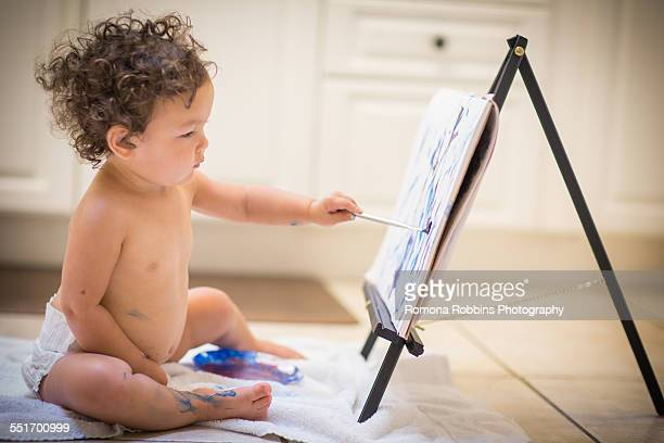 Little girl painting in kitchen