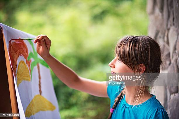 Little girl painting on easel in the garden