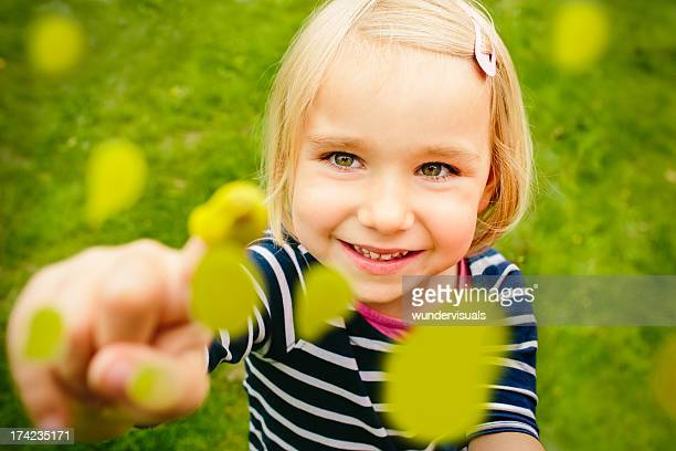 Little girl painting on glass with finger paint