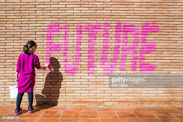 Little girl painting with pink colors the future word in a brick wall, a protest action claiming for future to the new generations.