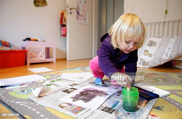 Little girl painting with watercolours on the floor of childrens room