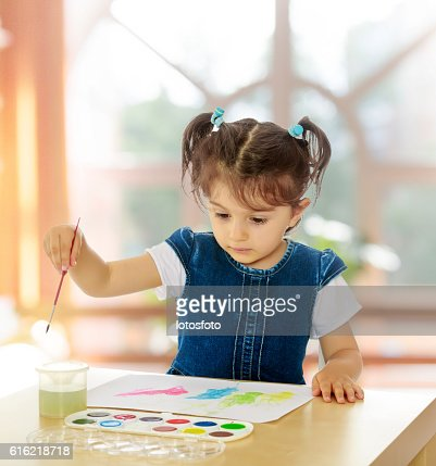 Little girl paints with watercolors at the table. : Stock Photo