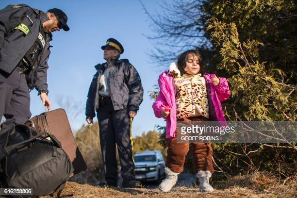 A little girl part of family of four from Pakistan stands close to RCMP officers after her family illegally crossed the USCanada border near...