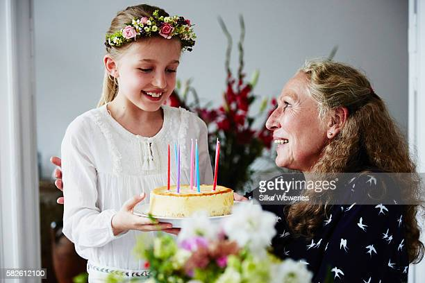 little girl passing a birthday cake to her grandmother