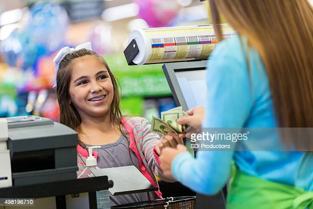 Little girl paying for purchases with cash in local store