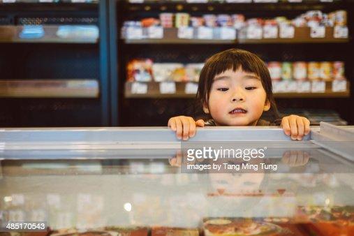 Little girl peeking into freezer in supermarket