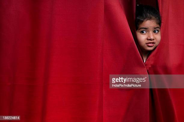 Little girl peeking out from the curtain