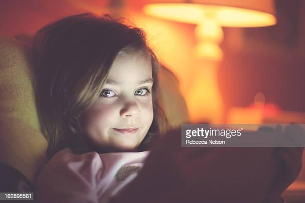 Little girl peeking over tablet