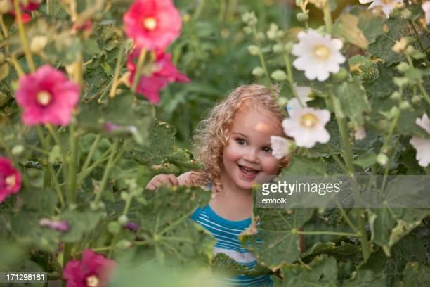 Kleine Mädchen Spähen durch Stockmalve Blumen
