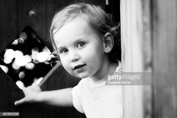 Little girl peering around the door