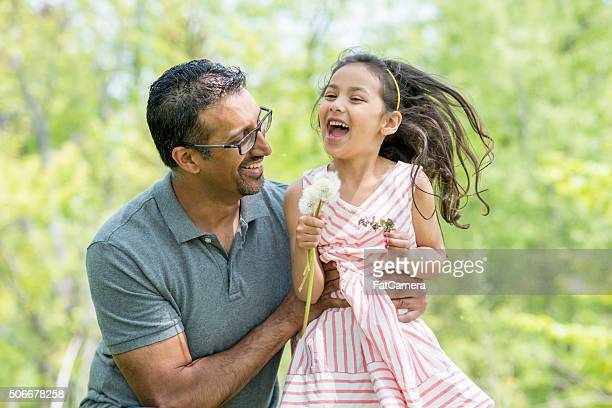 Little Girl Picking Flowers at the Park with Her Dad
