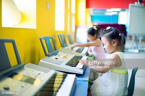 little girl play electronic organ in kindergarten