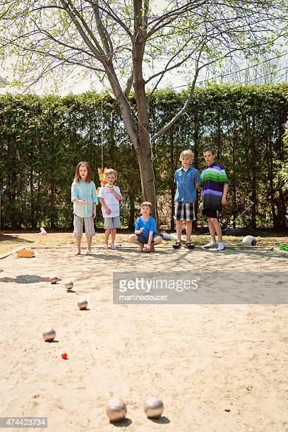 Little girl playing ball game outdoors with boys suburb backyard.