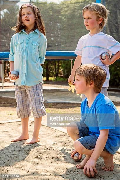 Petite fille jouant avec le jeu en plein air avec les garçons banlieue jardin.