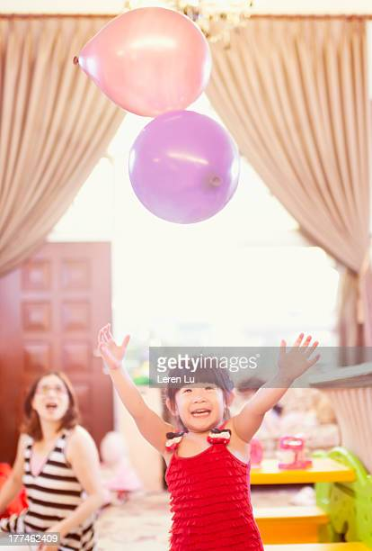 Little girl playing balloon in home