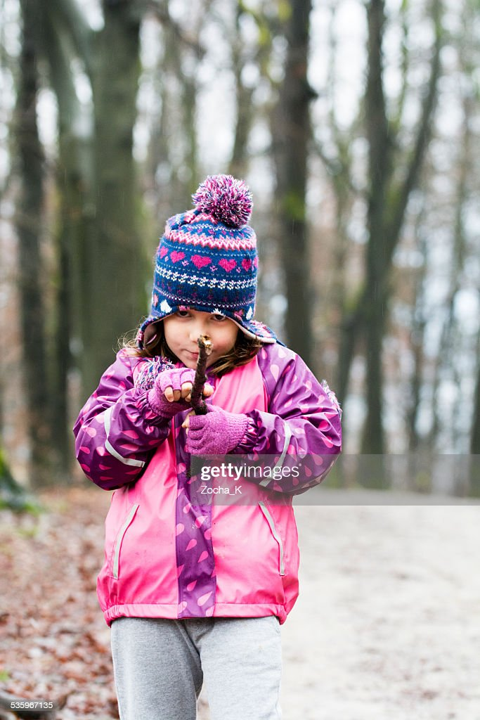 Little girl playing boy's games in forest on rainy day : Stock Photo