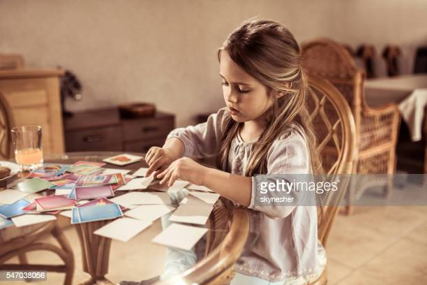 Little girl playing card memory game at the table.