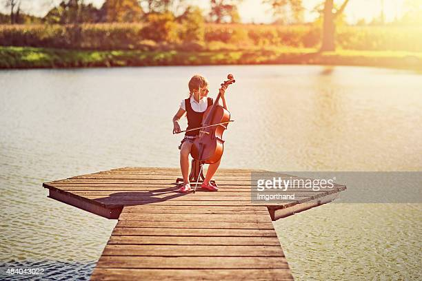 Little girl playing cello on pier