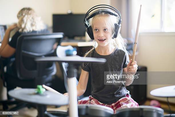 Little girl playing drums when her sister doing homework