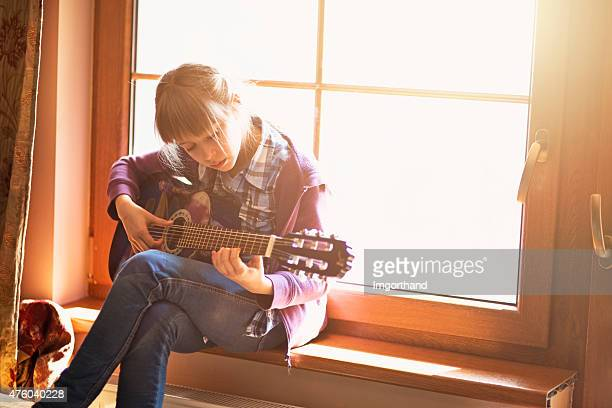 Little girl playing guitar sitting on window