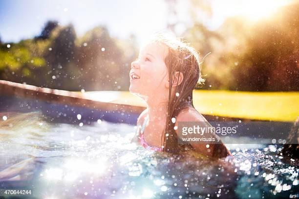 Little girl playing happily by herself in a swimming pool