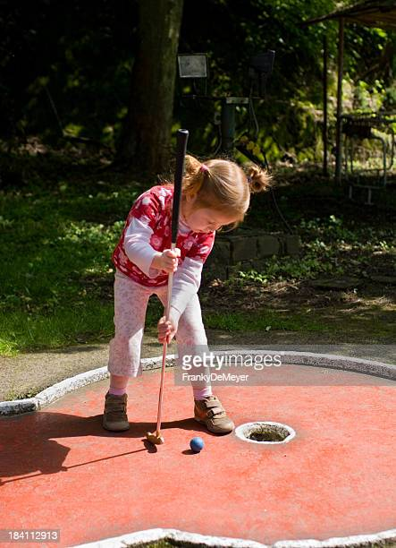 Little girl playing her first game of mini golf