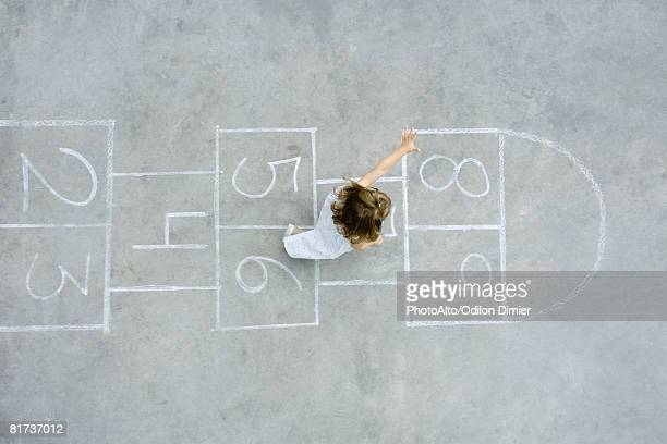 Little girl playing hopscotch, overhead view