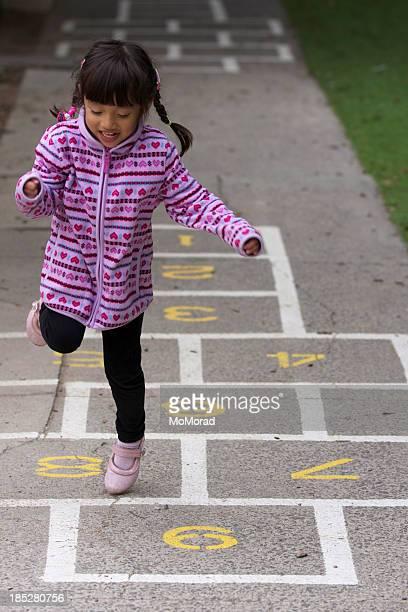 A little girl playing hopscotch
