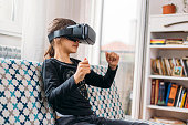 Little girl playing imaginary game with virtual reality headset