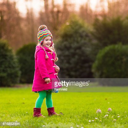 Little girl playing in autumn park : Stock Photo