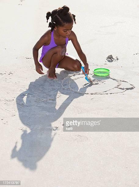 Petite fille jouant dans le sable à la plage