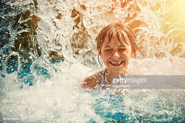 Kleines Mädchen spielen im Wasserfall im Wasserpark Schwimmbad