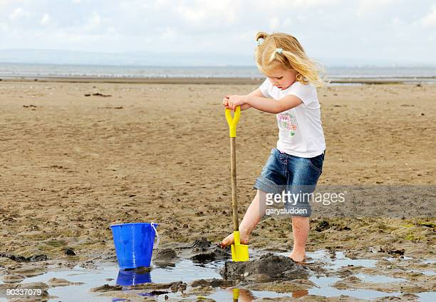 little girl playing on a polluted beach