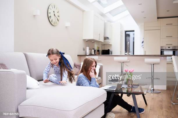 Little girl playing on couch while her mother talking via mobile phone