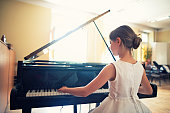Llittle girl playing on grand piano