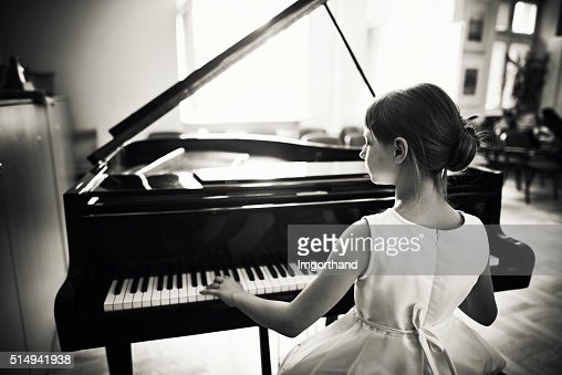 Little girl playing on grand piano